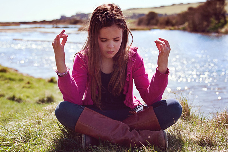 Girl meditating by water in yoga pose